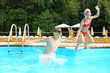 Happy boy and girl jumping into the swimming pool