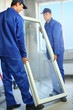 Two workers in blue work clothes carry the window