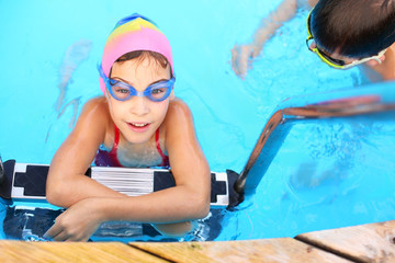 Smiling girl in blue goggles on the ladder in pool