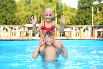 Smiling boy and girl playing in outdoor swimming pool