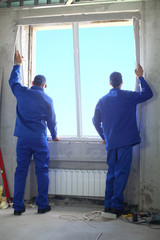 Two men in working clothes set new window frame