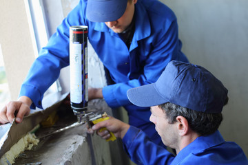 Two workers use mounting foam