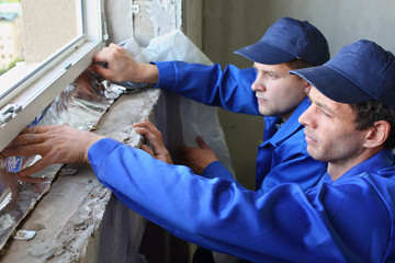 Two men in working clothes places foiled insulation