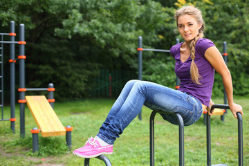 Young girl sitting on sports equipment
