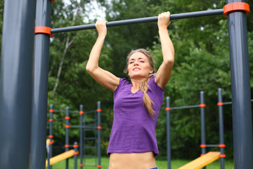 Young beautiful girl performing pull ups