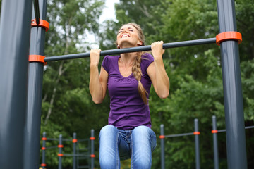 Young beautiful girl doing chin-ups