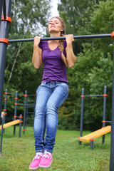 Young beautiful girl doing exercise on a horizontal bar