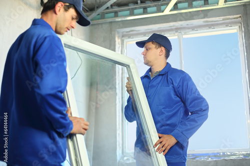 Two workers in blue work clothes set a new window