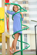 Girl in a striped dress on climbing pole at the playground