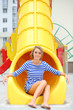Smiling girl sitting at bottom of yellow slide