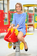 Smiling beautiful girl in a striped dress on a swing
