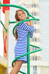 Smiling beautiful girl on climbing pole at the playground