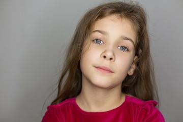 Portrait of little girl in red sweater in studio