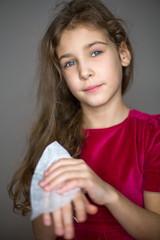 Little girl cleans hand by wet towel in studio