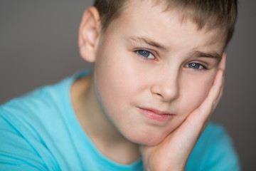 Portrait of a boy with a sad face in a blue T-shirt