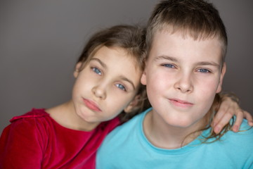 Portrait of sister and brother hugging in the studio