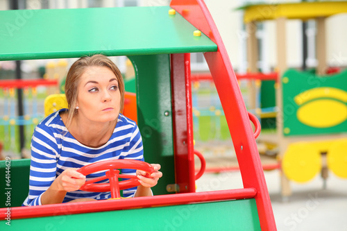 Funny girl sitting in a toy car on the playground