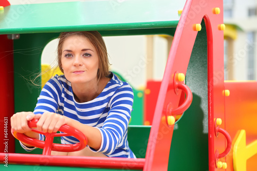 Girl imitate driving a car on the playground