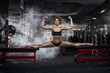 sporty strong fit young woman sitting on a full split In the gym