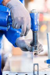 Handwerker nietet Metall in einer Werkstatt