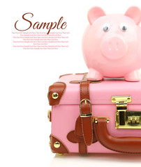 Pink suitcase with piggy bank and copy-space