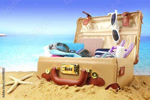 Full open suitcase on tropical beach background.