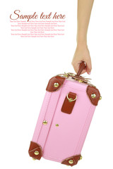Hand holding a pink travel suitcase isolated on white