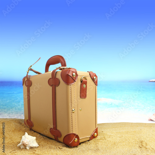 Closed suitcase on tropical beach background