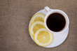 Cup of coffee with fresh lemon on the natural burlap