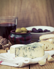 Cheese with olives, Nuts and Wine on Table