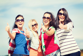 teenage girls or young women showing thumbs up