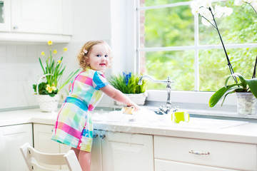 Adorable curly toddler girl in a colorful dress washing dishes