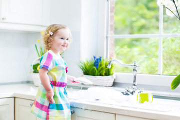 Cute curly toddler next sink in white kitchen