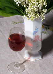 lily of the valley in vase and glass of wine