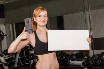 Sportliche Dame hält weißes Schild für Text / Daumen hoch
