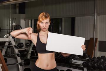 Sportliche Dame hält weißes Schild für Text / Daumen runter