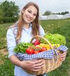 Junge Frau mit Gemüsekorb auf dem Feld