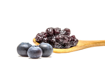A spoon of blueberry jam and three blueberries