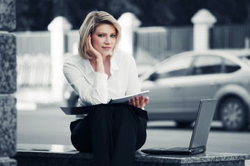 Young business woman with laptop at the office wall