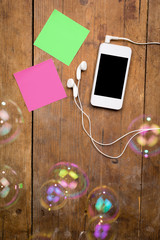 Smart phone with earphones and sticky notes on wooden surface