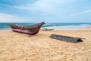 Traditional Sri Lankan fishing boat on empty sandy beach.