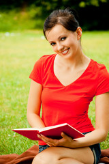 Young woman sitting on grass with book