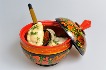 Boiled pelmeni in khokhloma painted russian wooden dishes with s