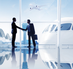 Two Businessmen Shaking Hands In An Airport