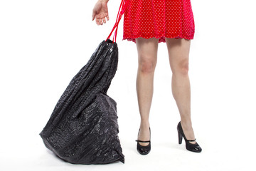 woman cleaning up and holding a black trashbag