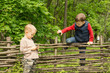 Young boy climbing over a rustic wooden fence
