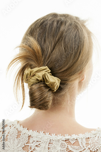 Leinwanddruck Bild Young woman with casual messy bun hairdo