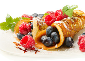 pancakes with raspberries and blueberies isolated on white