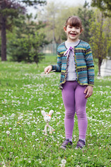 happy little girl play with white rabbit marionette doll