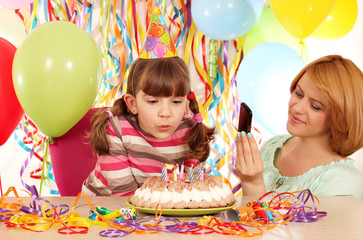 Mother taking picture while daughter blowing the candles on the